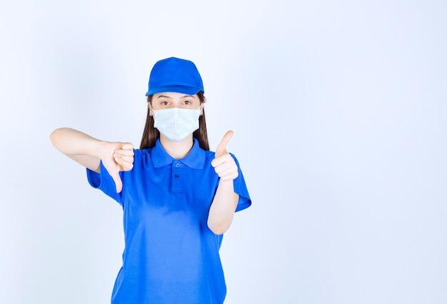 Foto van een vrouw in uniform en medisch masker met duim naar beneden.