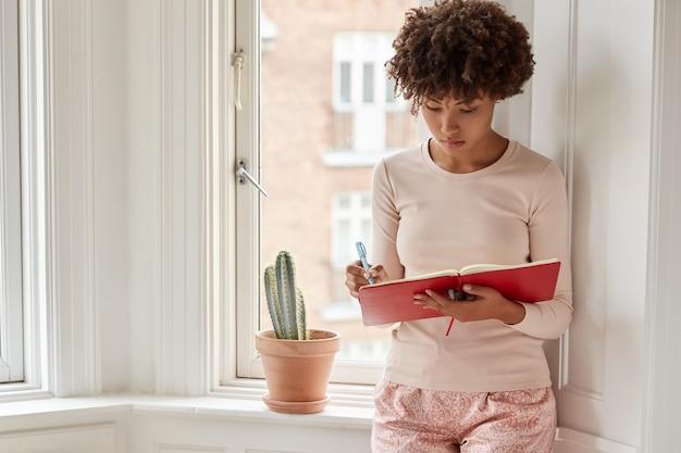 Foto van een vrouw met een donkere huid heeft een goed idee, schrijft in blocnote, draagt pyjama's