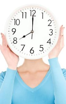 Foto van een vrouw met een grote klok die gezicht bedekt