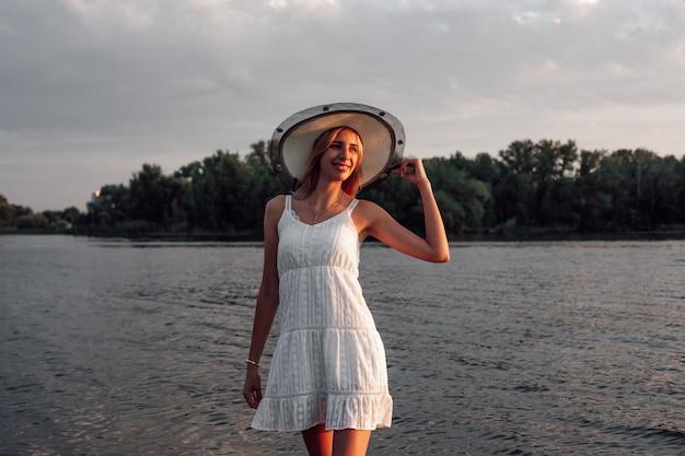 Foto van een vrouw met een strohoed, een mooie gelukkige jonge blonde in een witte zomerse kanten jurk en een st...