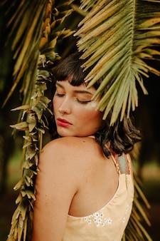 Foto van een vrouw onder palmbladeren met haar ogen dicht
