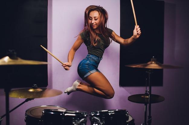 Foto van een vrouwelijke drummer die een drumstel speelt