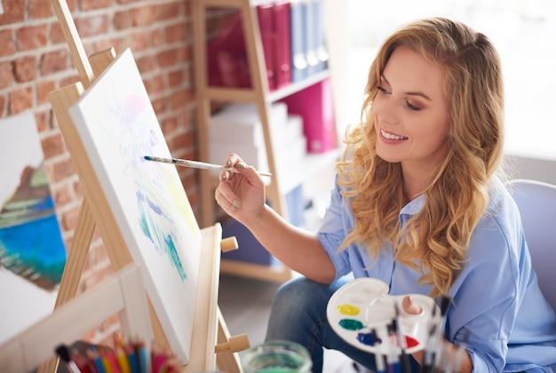 Foto van een vrouwelijke kunstenaar die naast een schildersezel zit