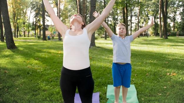 Foto van een vrouwelijke yogaleraar of goeroe van middelbare leeftijd die een tiener onderricht die yoga doet. vrouw met jongen die mediteert en zich uitstrekt op gras in het park