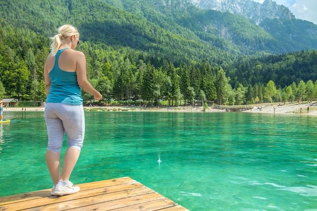 Foto van een vrouwtje op een houten brug tegen een smaragdgroen meer met een adembenemende natuur