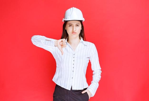 Foto van een zakenvrouw in veiligheidshoed met een duim naar beneden.