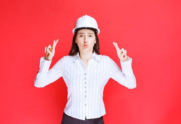 Foto van een zakenvrouw in veiligheidshoed met gekruiste vingers.