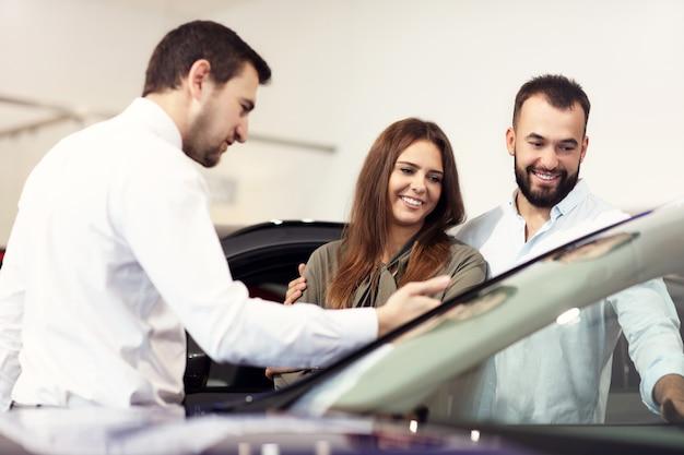 Foto van een zelfverzekerde jonge verkoper die alle autokenmerken uitlegt aan de jonge aantrekkelijke eigenaren attractive