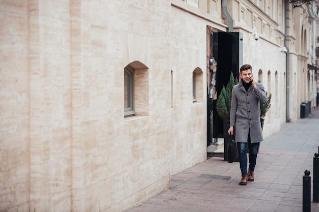 Foto van elegante man in jas met zak in de hand lopen door lege straat, en praten over smartphone