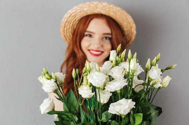 Foto van elegante vrouw jaren '20 met rood haar die strohoed dragen en bos van witte bloemeneustoma houden, die over grijze muur wordt geïsoleerd