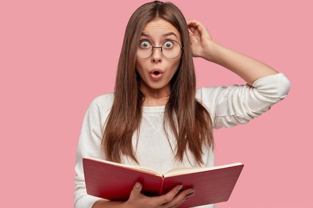 Foto van emotioneel verrast europees meisje krabt hoofd met verbijstering