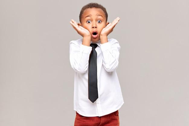 Foto van emotionele grappig verrast afro-amerikaanse schooljongen in overhemd en stropdas hand in hand op zijn gezicht, ogen wijd open en mond wijd open, geschokt door verbazingwekkend onverwacht nieuws