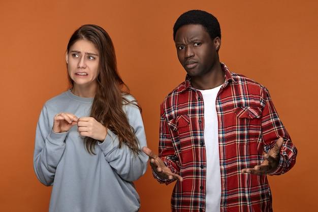 Foto van emotionele jonge langharige vrouw met nerveuze bezorgde uitdrukking terwijl ze zich schuldig voelt terwijl ze naast haar verwarde afro-amerikaanse vriend staat die niet begrijpt wat er mis is