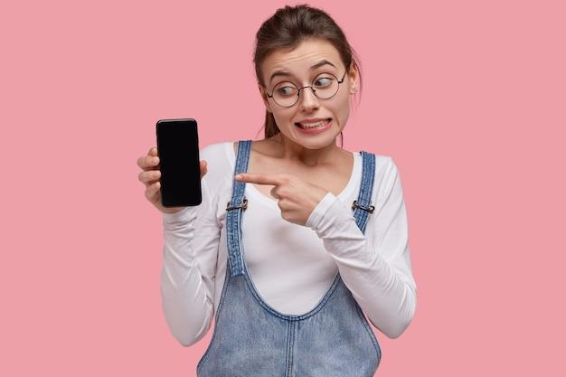 Foto van emotionele jonge vrouw wijst naar het scherm van de moderne gadget, aarzelt om slimme telefoon te kopen, kijkt verbijsterd