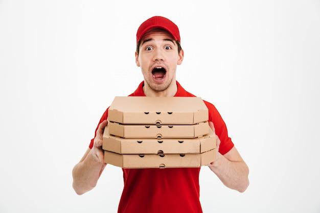 Foto van emotionele kerel van de leveringsdienst in rode t-shirt en glb-holdingsstapel pizzadozen, die over witte ruimte wordt geïsoleerd