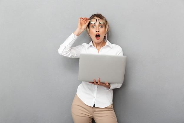 Foto van emotionele zakenvrouw die een bril draagt en laptop op kantoor houdt, geïsoleerd