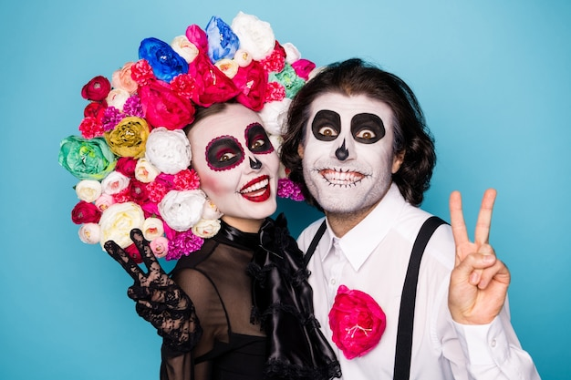 Foto van eng griezelig paar man dame knuffel show v-teken maak bericht foto levende opvolgers dragen zwarte jurk dood kostuum masker roos hoofdband jarretel geïsoleerde blauwe kleur achtergrond