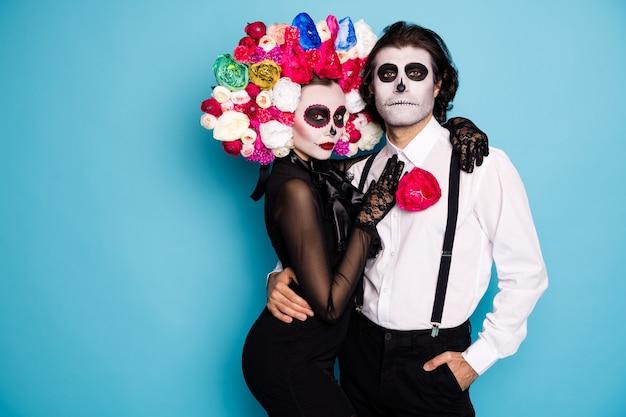Foto van eng paar man dame knuffelen besteden eeuwige huwelijksreis onderwereld wezens dragen zwarte jurk dood kostuum suiker schedel decor rozen hoofdband bretels geïsoleerde blauwe kleur achtergrond