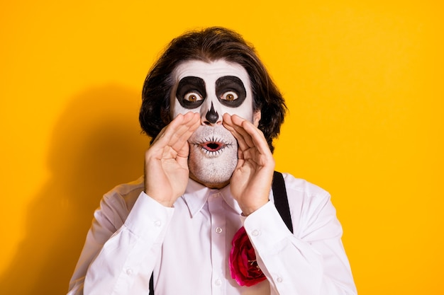 Foto van enge speelse sluwe demon met haren man hand mond opgewonden verspreiding nep feiten truc mensen val dragen wit overhemd roos dood kostuum bretels geïsoleerde gele kleur achtergrond