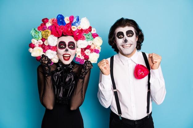 Foto van enge twee mensen man dame verrast vuisten opsteken winnen ondode rollenspel karakter concurrentie slijtage zwarte jurk dood kostuum rozen hoofdband bretels geïsoleerde blauwe kleur achtergrond