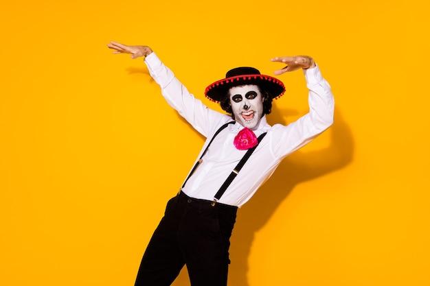 Foto van enge zombie schepsel man sprong schrik opheffen doen alsof handen boomtakken horrorfilm casting draag wit overhemd dood kostuum suiker schedel bretels geïsoleerde gele kleur achtergrond