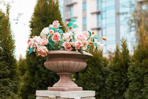 Foto van enkele mooie babyroze rozen in een stenen vaas buiten