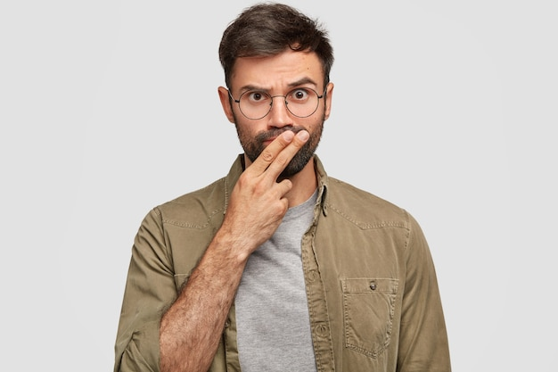 Foto van ernstige bebaarde jonge kerel houdt twee vingers op de mond, probeert een beslissing te nemen, kijkt met strikte uitdrukking, gaat iemand straffen, draagt vrijetijdskleding, geïsoleerd over witte muur