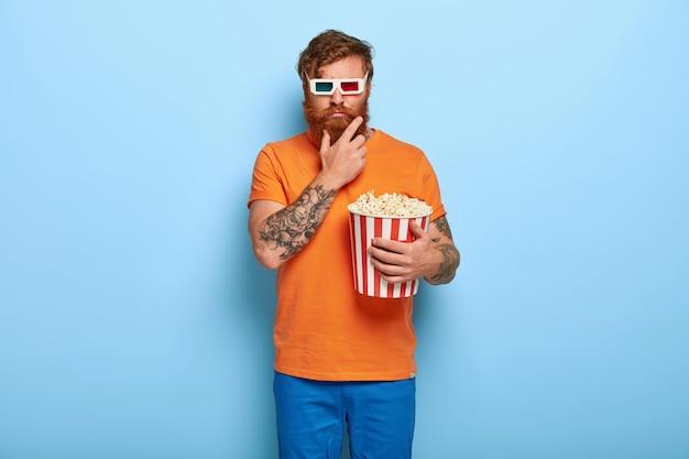 Foto van ernstige bebaarde roodharige man eet popcorn