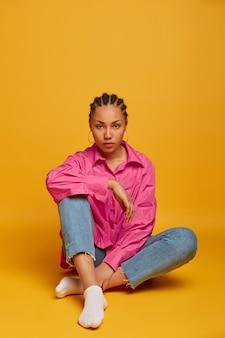 Foto van ernstige donkere vrouw heeft een informeel gesprek met iemand, poseert op de vloer tegen gele muur, ziet er direct uit, voelt zich moe na de training, leidt een actieve levensstijl. schot