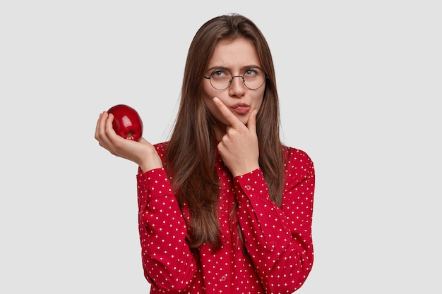Foto van ernstige doordachte mooie vrouw houdt kin, draagt appel, heeft contemplatieve uitdrukking, draagt een rood shirt