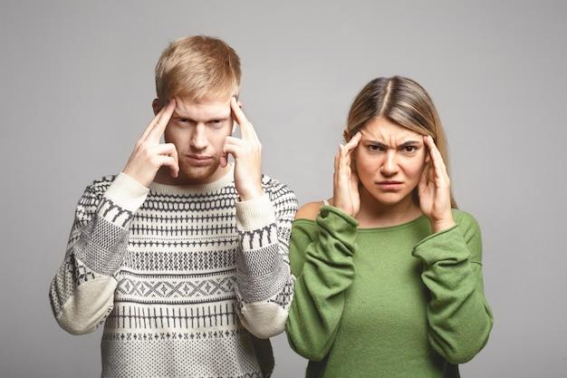 Foto van ernstige geconcentreerde jonge man en vrouw in vrijetijdskleding die fronsend en in hun slapen knijpen alsof ze zich iets proberen te herinneren of vreselijke hoofdpijn hebben. menselijke gezichtsuitdrukkingen