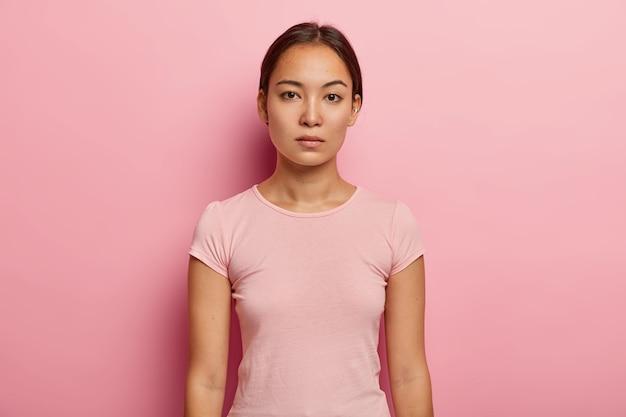 Foto van ernstige rustige vrouw met donker haar, gekleed in vrijetijdskleding, ziet er recht uit, heeft frisse huid, draagt piercing in het oor