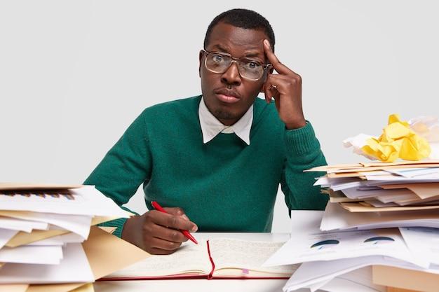 Foto van ernstige stijlvolle afgestudeerde student houdt de hand op de tempel, zit op het bureaublad, schrijft notities in kladblok, draagt een transparante bril voor zichtcorrectie