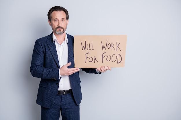 Foto van ernstige trieste arme dakloze werkloze ontslagen man lijdt financiële crisis verloren werk houd plakkaat zoekwerk voor wat voedseluitwisseling draag blauw pak geïsoleerde grijze achtergrond