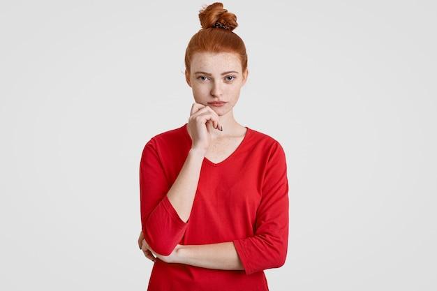 Foto van ernstige vrouw met rood haar gekamd in broodje, houdt kin, houdt handen gedeeltelijk gekruist, kijkt serieus naar de camera, denkt over iets belangrijks, geïsoleerd op wit. gedachten