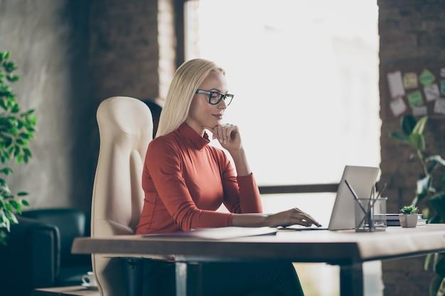 Foto van ernstige zekere peinzende vrouw die laptop onderzoekt die jaarlijks inkomen voor vorig jaar vergelijkt met huidige die bril draagt