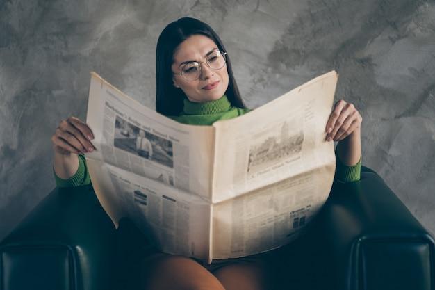 Foto van ernstige zelfverzekerde geconcentreerde vrouw die in leunstoel zit die door krantenkoppen kijkt die geïsoleerde grijze muur concrete achtergrond lezen