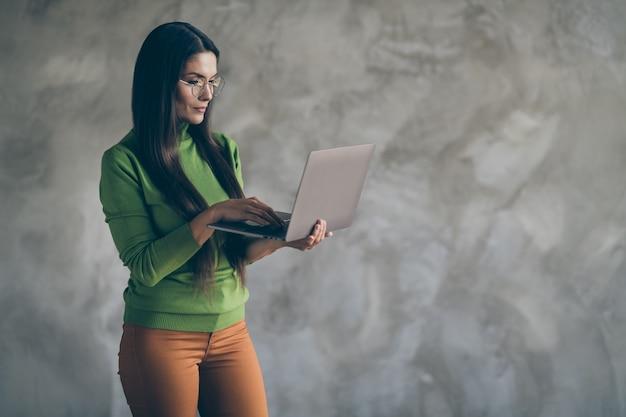 Foto van ernstige zelfverzekerde slimme slimme vrouw browsen door laptop in oranje broek typen om de nodige informatie te vinden geïsoleerde grijze muur betonnen achtergrondkleur