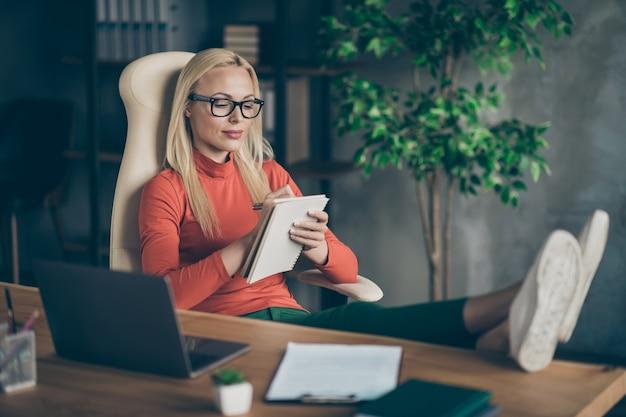 Foto van ernstige zelfverzekerde vrouw die notitieboekje onderzoekt dat haar gedachten opschrijft, moest worden gebruikt bij het opstarten met voeten op het bureaublad