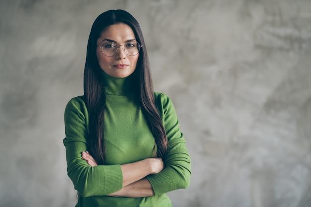 Foto van ernstige zelfverzekerde vrouw met gevouwen handen naar je kijken aandachtig haar intelligentie tonen in de buurt van lege ruimte geïsoleerde grijze kleur muur betonnen achtergrond