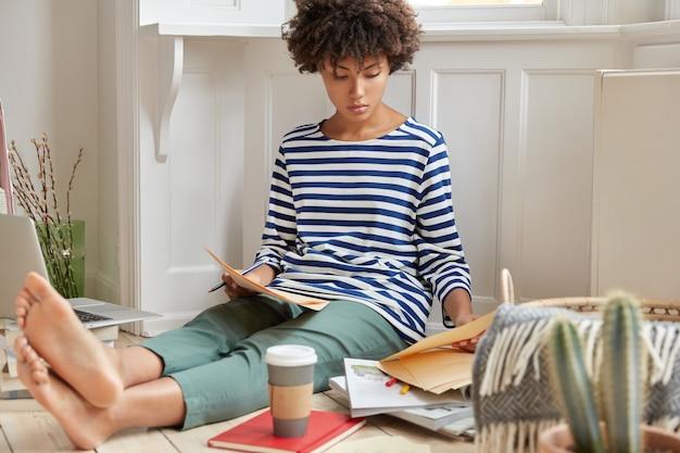 Foto van ernstige zwarte jonge vrouw analyseert contract, aromatische koffie drinkt, heeft een attente blik