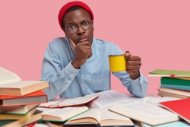 Foto van ernstige zwarte man houdt kin, draagt gele mok drank, kijkt rechtstreeks naar camera, draagt rode hoed en shirt