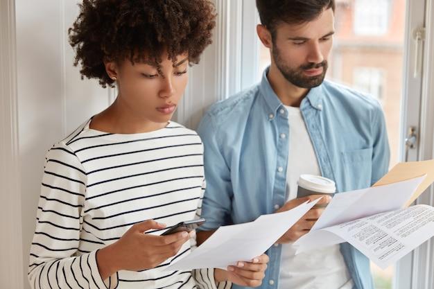 Foto van ernstige zwarte vrouw bestudeert checklist, gebruikt rekenmachine op mobiele telefoon, ongeschoren man met haren houdt koffie, leert werkaudit, stelt jaarlijks financieel verslag op, controleert inspectie