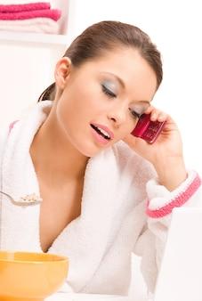 Foto van etende vrouw met mobiele telefoon