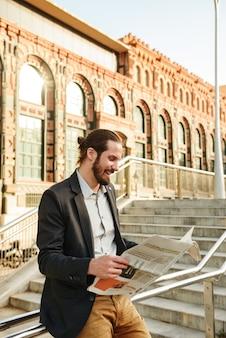 Foto van europese bebaarde man 30s in klassiek pak, wandelen in stadsstraat en krant lezen over economie op stadstrap