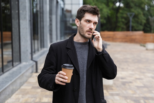 Foto van europese man 20s met behulp van mobiele telefoon, terwijl buiten wandelen met afhaalkoffie
