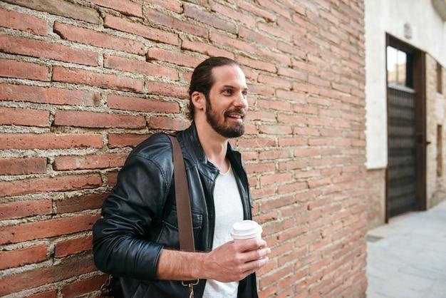Foto van europese ongeschoren man met vastgebonden haar staande over bakstenen muur op straat in de stad en afhaalmaaltijden koffie drinken