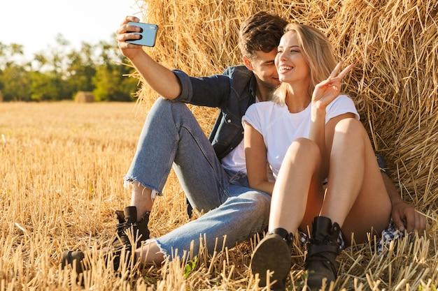 Foto van europese paar man en vrouw selfie zittend onder grote hooiberg in gouden veld, tijdens zonnige dag