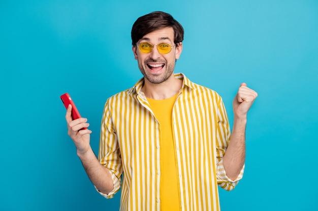 Foto van extatische man blogger gebruik smartphone vieren reizen vakantie sociaal netwerk loterij winnen vuisten opsteken dragen gestreept geel wit overhemd geïsoleerde blauwe kleur achtergrond