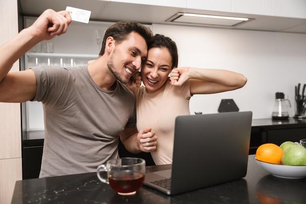 Foto van extatische paar man en vrouw met behulp van laptop met creditcard, zittend in de keuken